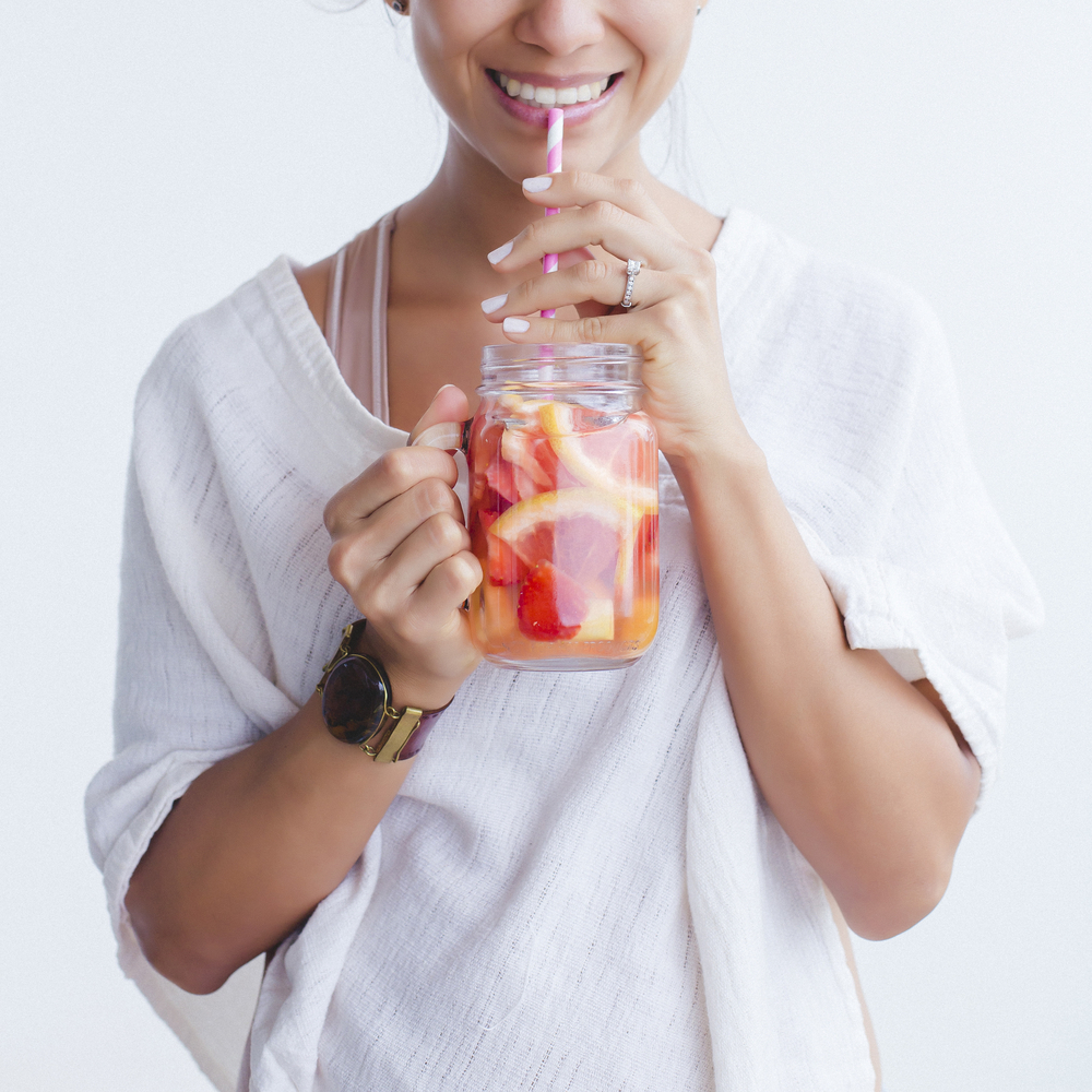 Woman,Drinking,An,Orange,And,Grapefruit,Infused,Water,In,Mason